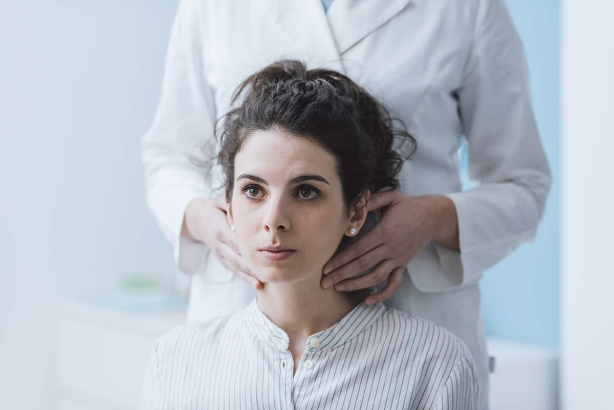 Woman having thyroid checked by doctor