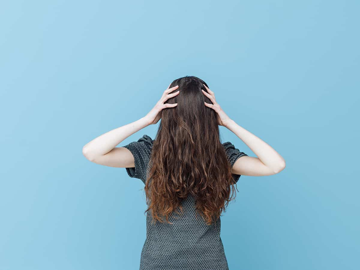 Woman with face covered behind her hair