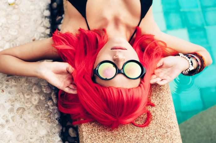 girl with red hair wig in black bikini and sunglasses