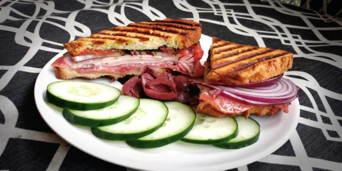 grilled sandwich with lunchmeat with cucumber slices and olives on a graphic background