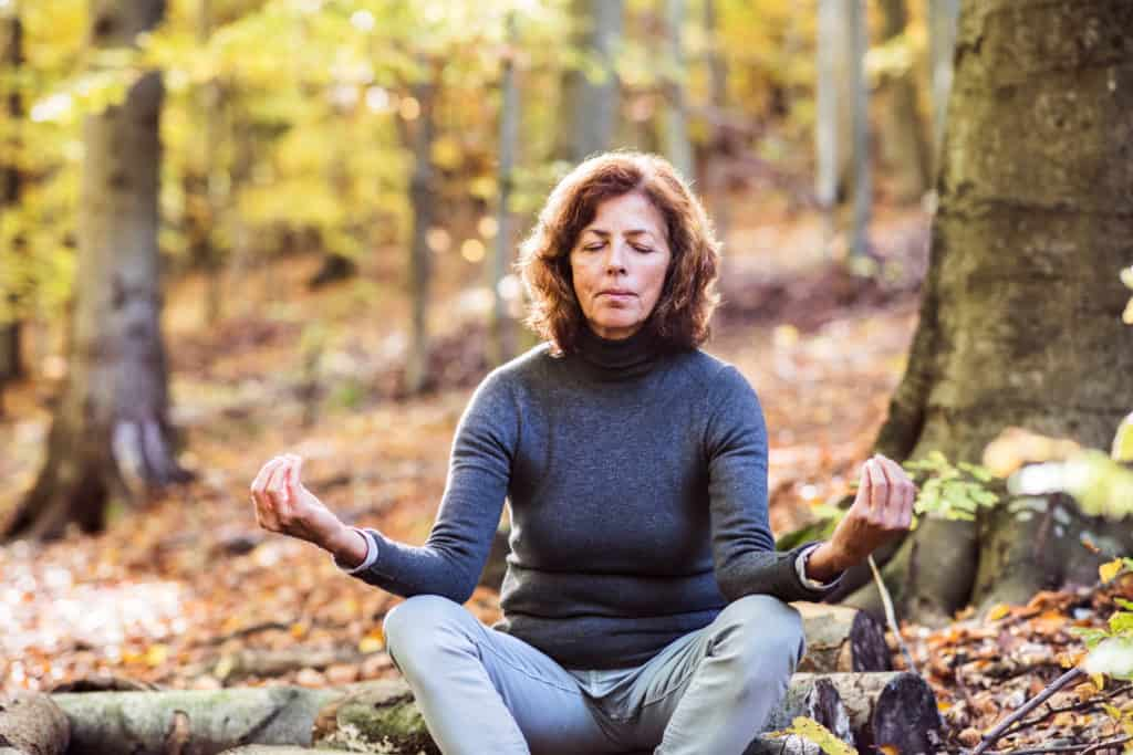 mid-aged woman sitting on a log in the woods meditating