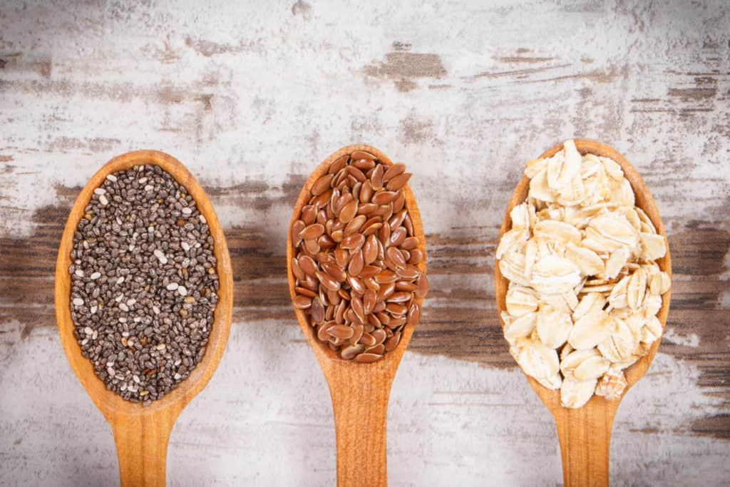 spoons with chia seeds, flax seeds, and oats