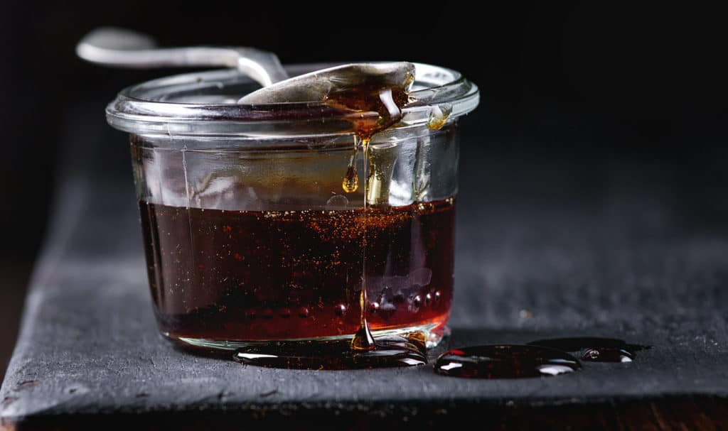 Homemade liquid transparent brown sugar caramel in glass jar standing on black wooden board with spoon. Close up