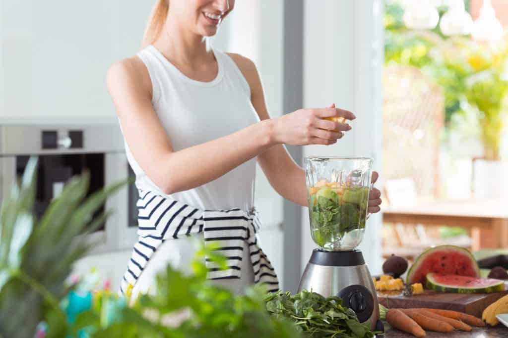 Happy vegan woman mixing a healthy smoothie with green vegetables