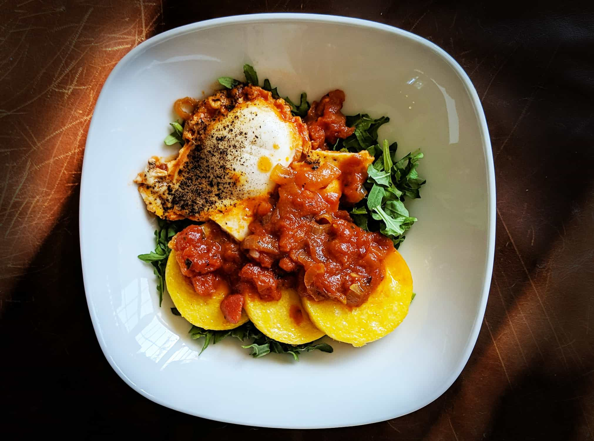 One white plate viewed from above containing one cooked egg, three slices of polenta, red marinara sauce, and some pops of green arugula.