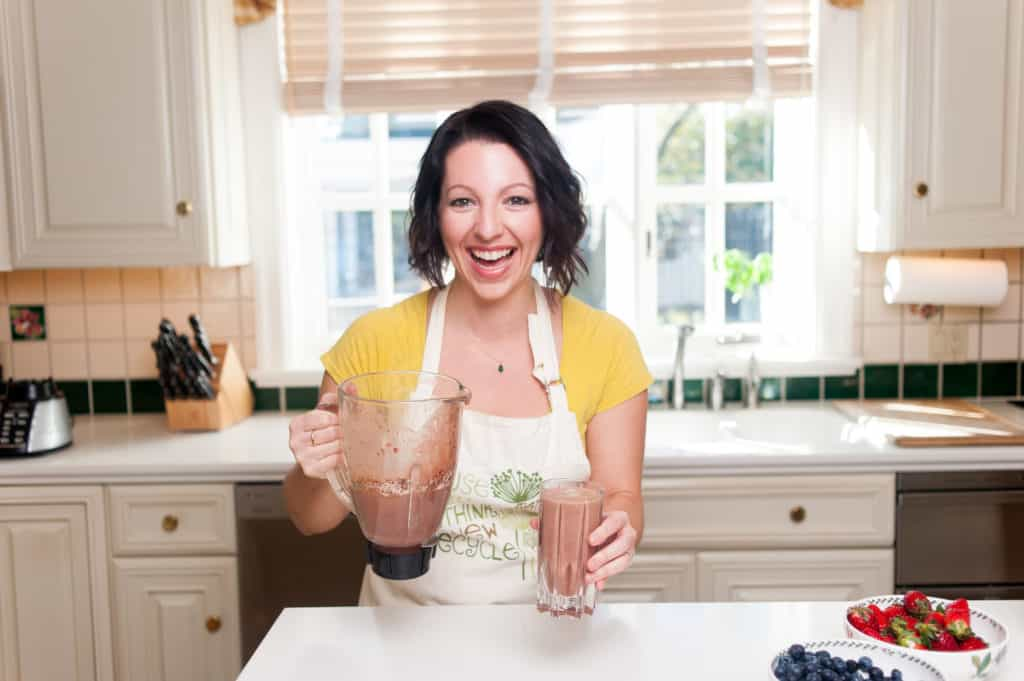 woman laughing holding a blender in one hand and a smoothie in the other hand in a white kitchen