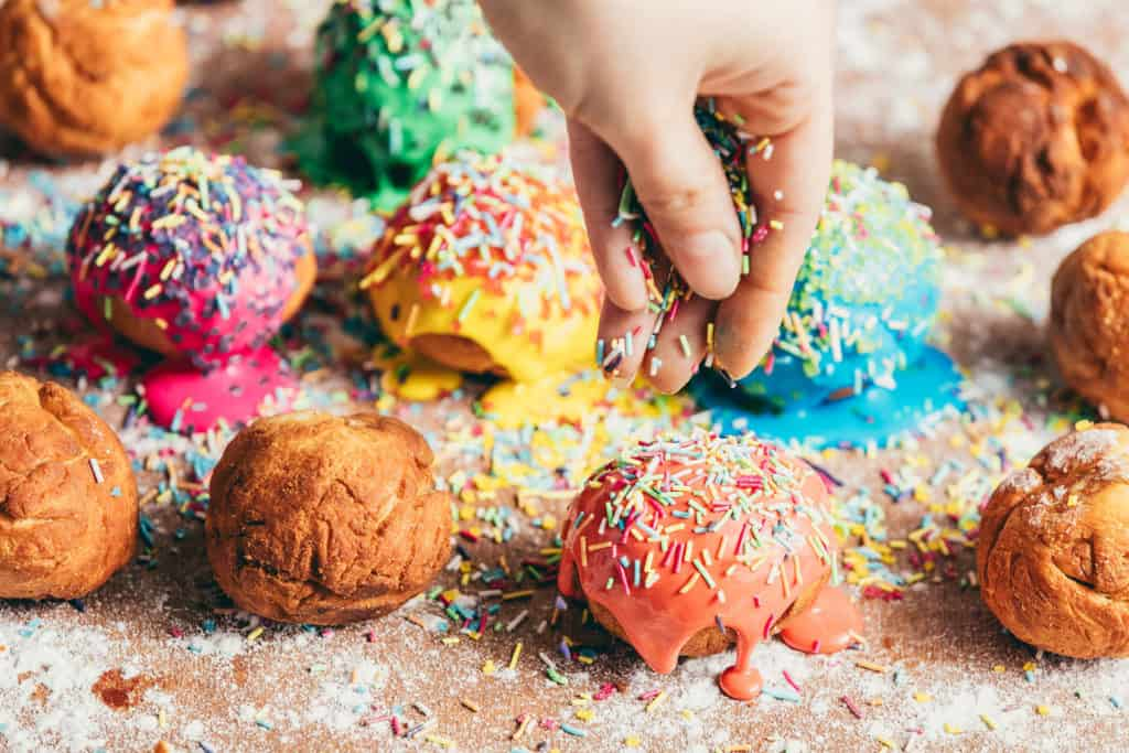 Woman's hand sprinkling sugar sprinkles on colorful donuts. Decoration process.