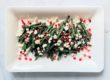 roasted green beans with crumbled goat cheese and pomegranate seeds on a white rectangular plate and light grey background