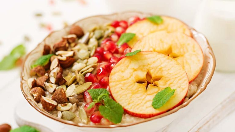 Tasty and healthy oatmeal porridge with apples, pomegranate and