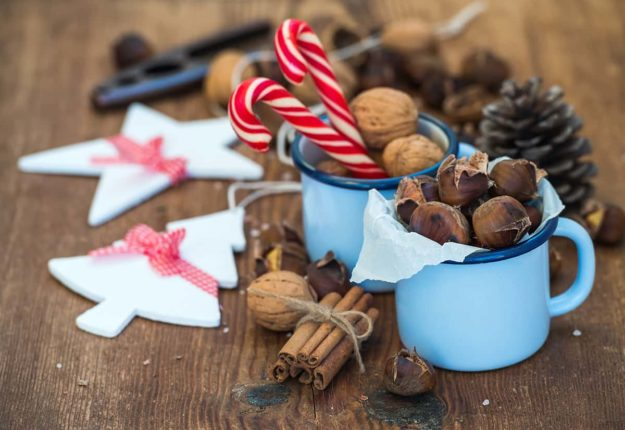 Traditional Christmas foods and decoration. Roasted chestnuts in blue enamel mug, walnuts, cinnamon sticks, candy canes, pine cone on rustic wooden background