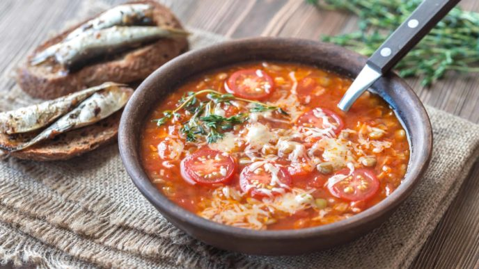 Portion of green lentil tomato soup with toasts