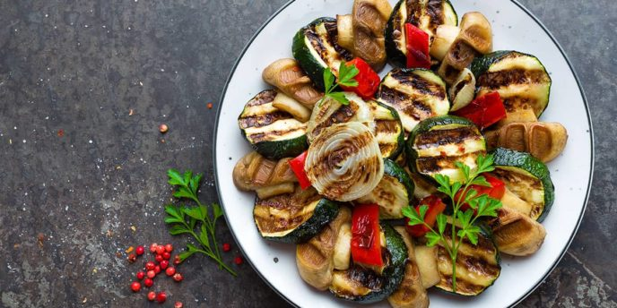 Salad with grilled vegetables and mushrooms. Vegetable salad with grilled champignons. Grilled salad on plate