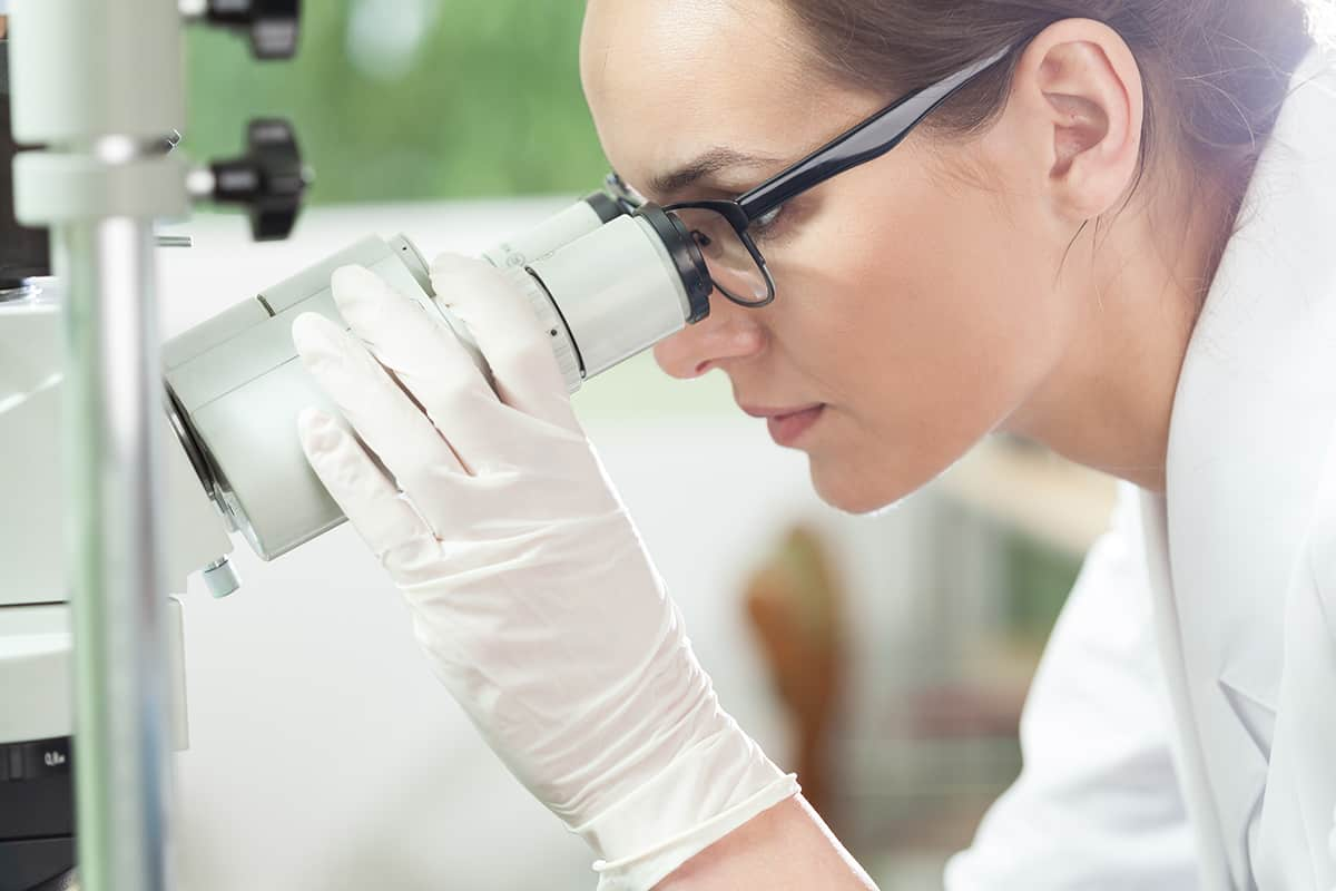 Woman using microscope in laboratory