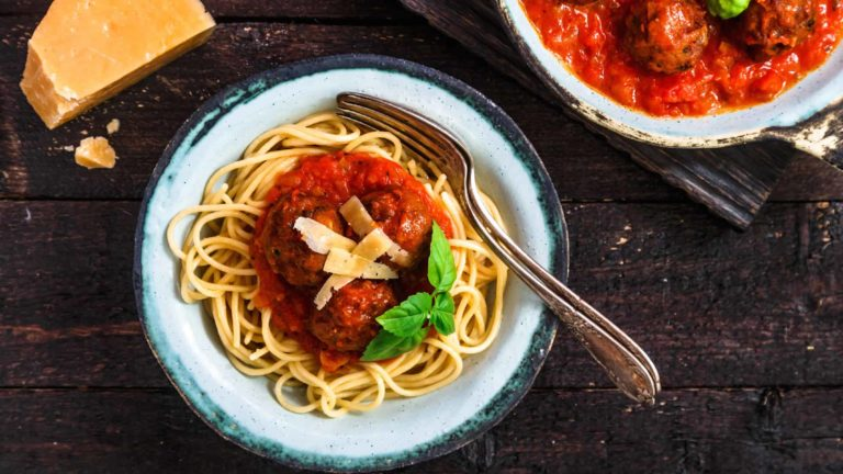 Pasta with meatballs and spicy marinara sauce and cheese, top view, rustic style.