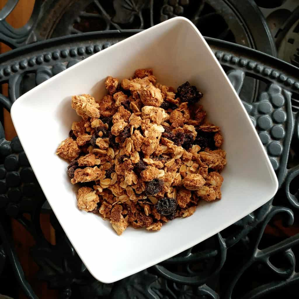 Top view of cashew butter granola in a white bowl on a grey background