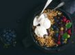 Oat granola crumble with fresh berries, seeds and ice-cream in iron skillet pan on dark wooden board over black backdrop