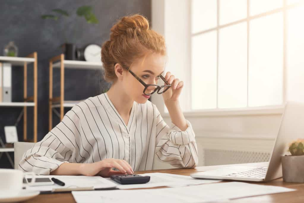 Financier woman in glasses working on laptop and counting financial accounts in office. Concentrated female manager working on marketing strategy at workplace