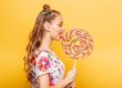 Beautiful young woman addicted to sugar with playful look eating huge candy and smiling. Stylish girl with blonde curly hair. Portrait of attractive lady with big lollypop, yellow wall on background.