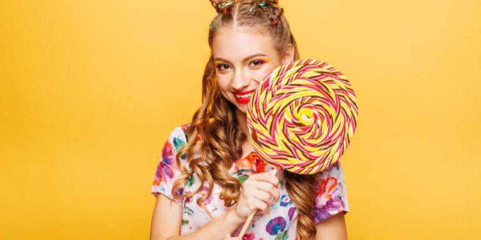 Beautiful young woman with huge candy instead of a head. Big colorful caramel lollypop in hands of woman. Portrait of attractive lady with big lollypop, yellow wall on background.